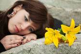 Young woman with a flowers lying on the tombstone — Stock Photo