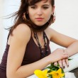 Sad young woman with a flowers — Stock Photo