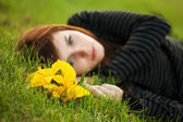 Sad young woman with a flowers lying on the grass — Stock Photo
