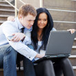 Young business couple using laptop on the steps — Stock Photo