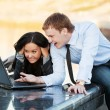 Young business couple using laptop — Stock Photo #27343797