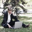 Businesswoman using laptop in a city park — Stock Photo