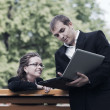 Young business people with laptop in a city park — Stock Photo