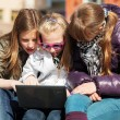 Stock Photo: Teenage schoolgirls using laptop on bench