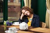 Szczęśliwa młoda kobieta picia herbaty w restauracji — Zdjęcie stockowe
