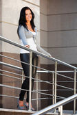 Beautiful young woman leaning on the handrail — Stockfoto