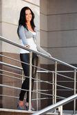 Vacker ung kvinna lutar på ledstången — Stockfoto