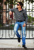 Young man at the cast iron fence — Stock Photo