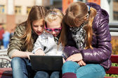 Teenage schoolgirls using laptop on the bench — Stock Photo