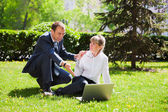 Young business people with laptop — Stock Photo