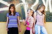 Tienermeisjes tegen een graffiti — Stockfoto