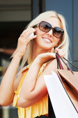 Young woman with shopping bags calling on the phone — Stock Photo