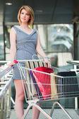 Mujer joven con carrito de compras — Foto de Stock