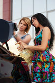 Young women loading shopping bags in a car trunk — Photo