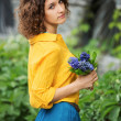 Sad young woman with bouquet of flowers — Stock Photo