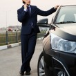 Young businessman calling on the phone at the car — Stock Photo