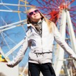 Happy teenage girl against a ferris wheel — Stock Photo