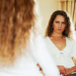 Beautiful woman looking at herself in the bedroom mirror — Stock Photo