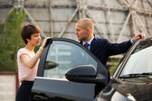Young business couple talking at the car — Stock Photo