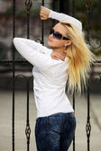Blond woman at the cast iron fence — Stock Photo