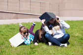 Teenage schoolgirls lying on a grass — Stock Photo