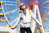 Happy teenage girl against a ferris wheel — Stock Photo