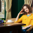 Sad young woman drinking tea at restaurant — Stock Photo