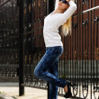 Blond womat cast iron fence — Stock Photo #33971579