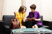 Two young women sitting on a couch in showroom — Stock Photo