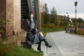 Ledsen ung kvinna i klassisk rock sitter på väggen — Stockfoto