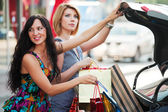 Two young women with a shopping bags at the car — Stockfoto