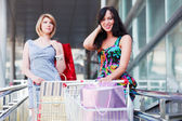 Young women with shopping cart — Stock Photo