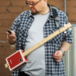 Man with a cigar box guitar looking at cell phone — Stock Photo