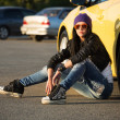 Fashionable punk woman sitting on the car parking — Stock Photo