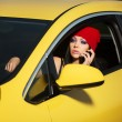 Young woman calling on cell phone in a car — Stock Photo