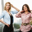 Two happy young women standing on the bridge — Stock Photo