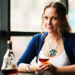 Beautiful young woman drinking cognac at restaurant — Stock Photo