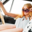 Young blonde woman relaxing in a retro car — Stock Photo