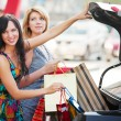 Two young women with shopping bags at the car — Stock Photo #36693907
