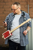 Man with a cigar box guitar looking at cell phone — ストック写真