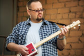 Man playing his three string cigar box guitar — Foto Stock
