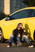 Sad fashionable punk woman sitting at the car — Stock Photo