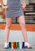 Pequeños bolsos de compras entre una mujer piernas — Foto de Stock
