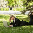 Stock Photo: Happy business woman using laptop in a city park