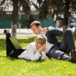 Stock Photo: Young business people using laptop in a city park