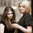Young women looking at mobile phone — Stock Photo #42065151