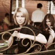 Stock Photo: Two young women at sidewalk cafe