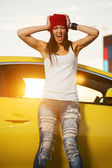 Angry fashionable punk woman standing at the car — Stockfoto