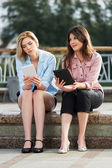 Two young women holding a digital tablet computers — Stockfoto