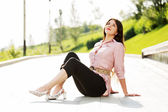 Happy young woman sitting on the sidewalk — Stock Photo